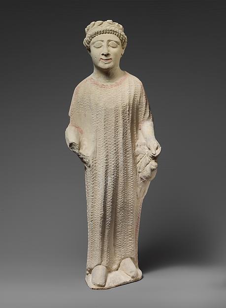 Limestone statuette of a boy holding a dove