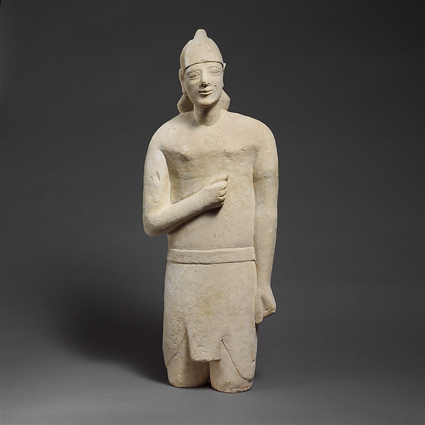 Limestone statuette of a beardless male votary in Egyptianizing dress wearing a helmet