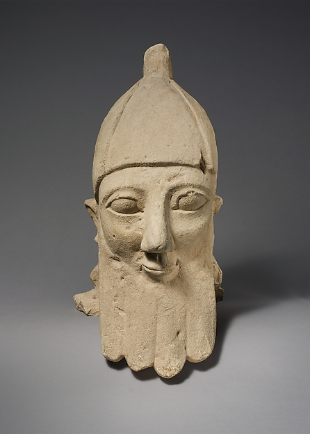 Over-lifesize bearded head wearing a conical helmet
