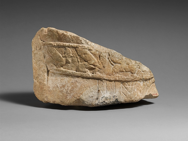 Fragment of an male limestone votary with an Egyptianizing kilt