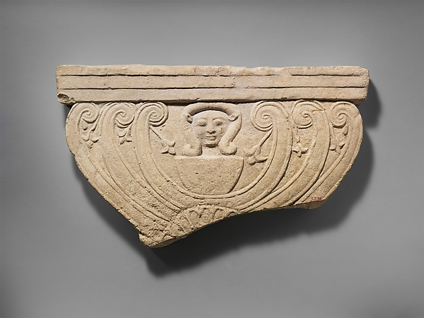 Limestone finial of a funerary stele with volutes and the head of Hathor