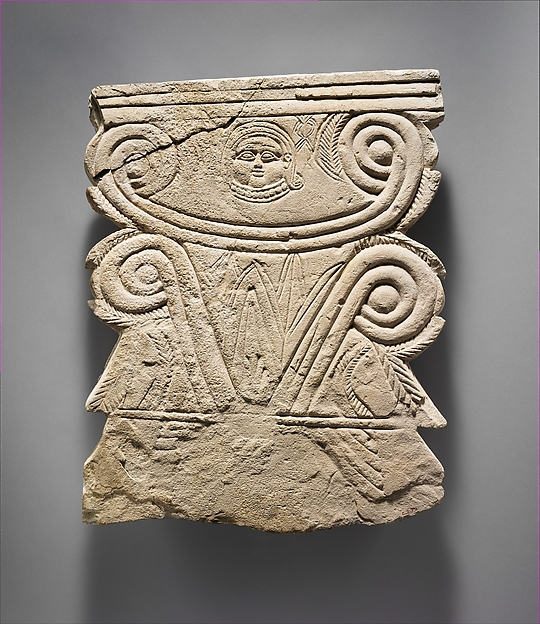 Limestone funerary stele with volutes and a Hathor head