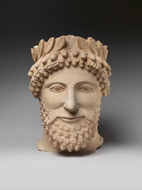 Limestone head of a bearded man wearing a wreath