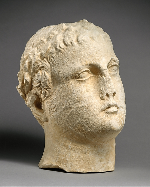 Limestone head of beardless male votary with wreath of leaves
