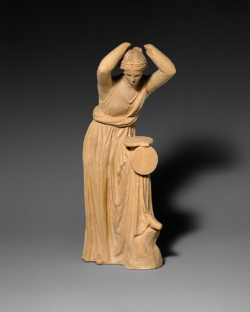 Terracotta statuette of a woman looking into a box mirror