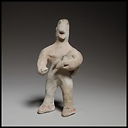 Standing male figurine holding a quadruped