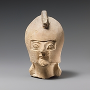 Limestone head of a warrior wearing a crested helmet