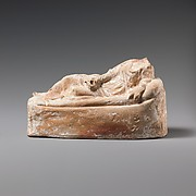 Terracotta statuette of a woman reclining on a couch