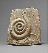 Fragmentary limestone relief with a snake and dolphin