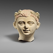 Limestone head of a boy with a wreath of leaves