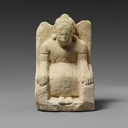 Limestone statuette of a seated beardless male votary with a helmet