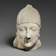 Limestone head of a beardless male wearing a conical helmet