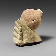 Limestone hand holding a pomegranate
