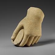 Limestone hand holding a pyxis