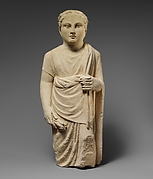 Limestone statuette of a boy holding a pyxis and a branch of leaves