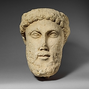Limestone head of a bearded male with a wreath of leaves