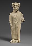 Limestone statuette of a boy with a flat headdress