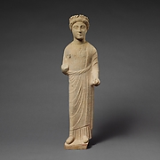 Limestone statuette of a beardless male votary with a wreath of leaves