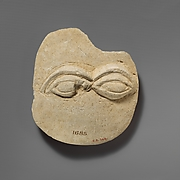 Limestone plaque with two eyes in relief