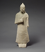 Statuette of a beardless male votary wearing a long garment and a conical helmet