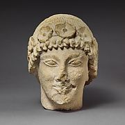 Limestone beardless male head with a wreath of rosettes