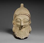 Limestone head of a bearded male wearing a conical helmet