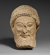 Limestone head of a bearded male with a wreath of flowers