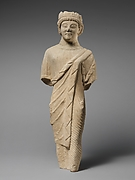 Limestone statuette of a beardless male votary in Greek dress with a wreath of leaves