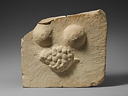 Limestone plaque with breasts and a bunch of grapes in relief