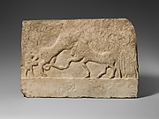 Limestone votive relief with a lion killing a bull and two human figures