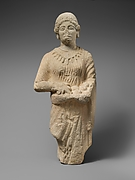 Limestone statuette of a female votary holding pieces of fruit