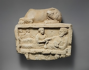 Limestone finial of a funerary stele with a recumbent lion and a banquet scene