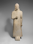 Limestone votary of a beardless male wearing a long garment and a conical helmet