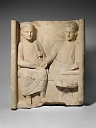 Limestone funerary stele with banquet scene