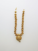 Necklace with bulla and gold beads