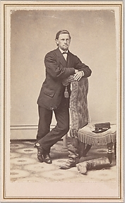 [Young Man, Standing, beside Empty Chair with Civil War Kepi on Seat, and Worn Boots, in Studio]