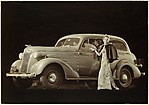 [Advertisement for Chevrolet: Woman in Evening Gown in front of a Chevrolet]