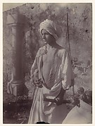 [Young Man in White Robe and Head Gear Holding Scabbard, Sicily, Italy]