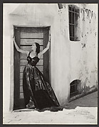[Woman in Long Dress, Standing in Doorway of Stuccoed Building]