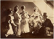 [A Group of Six Costumed Women Posed in Interior with Top Hatted Gentlemen]