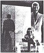 [Man in Suit Standing Behing Seated Woman in Suit]