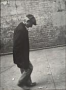 [Elderly Man in Dark Jacket and Cap Walking on Street, New York]
