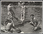 [Eastman Kodak Advertisement: Summer Lake Scene of Teenager with Camera Making a Snapshot of Her Friends in Bathing Suits on a Dock]