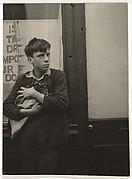 Garçon avec un chat dans les bras appuyé contre une vitrine