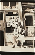 [Man Seated Outside Barber Shop, Vicksburg, Mississippi]