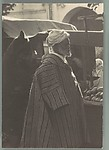 [Man in Traditional Moroccan Costume at Street Fruit Stand, Tangiers, Morocco]