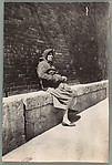 [Woman Seated on Ledge against Brick Wall, Cartagena, Spain]
