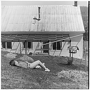 [Boy Lying on Ground in Front of House]