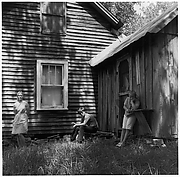 [Woman Leaning Against House Façade, Boy Seated, and Girl Leaning Against Shed]