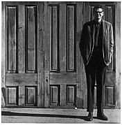 [Man Standing in Front of Three Wooden Doors]